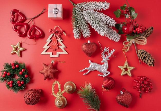 Świąteczne dekoracje świąteczne i noworoczne z kulkami, szyszkami i zabawkami na czerwonym tle.