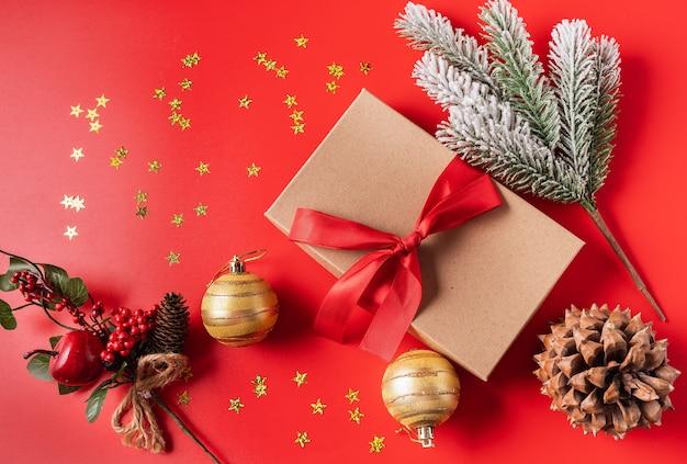 Świąteczne dekoracje świąteczne i noworoczne z pudełko, stożek, kulki i gałąź nowego roku drzewa na czerwonym tle.