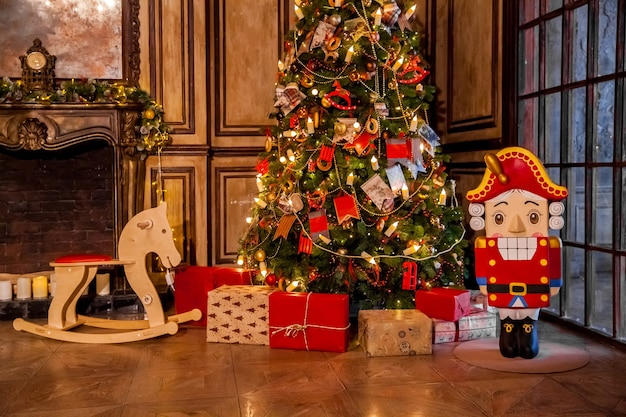 Świąteczne dekoracje w grunge wnętrzu pokoju z kominkiem, koń bujany fotel dla dzieci, klasyczna choinka z prezentami