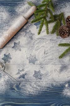 Świąteczne dekoracje w tle. ciasteczka w kształcie gwiazdy. mąka i przyprawy do świątecznych wypieków na ciemnym tle.