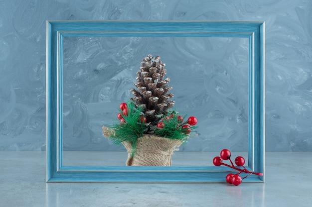 Świąteczne dekoracje wykonane z szyszki i pustej ramki na zdjęcia na marmurowym tle. wysokiej jakości zdjęcie