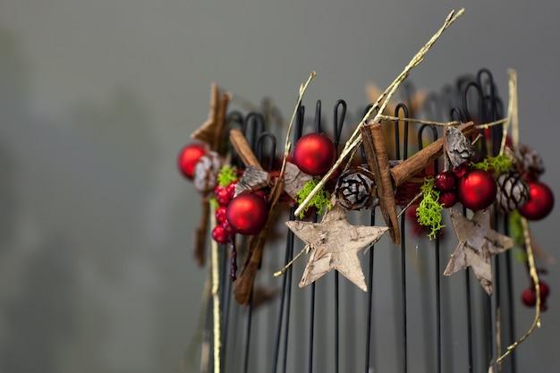 Świąteczne dekoracje z metalowymi prętami i szyszkami jodły złote gwiazdy szare tło