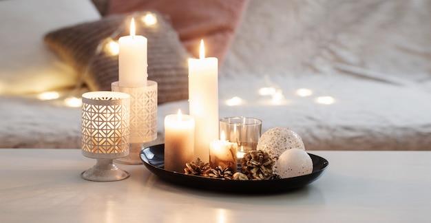 Świąteczne dekoracje z płonącymi świecami na białym stole przed kanapą z pledami i poduszkami.