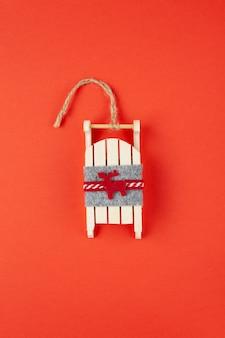 Świąteczne dekoracje, zabawki drzewa, drewniane sanki z jeleniem na czerwonym tle, dla mediów społecznościowych. świąteczny, nowy rok