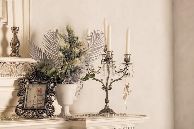 Świąteczne dekoracje ze świecami na półce. biała ściana. srebrne świeczniki retro z białymi świecami. stonowany obraz retro. wnętrze skandynawskiego pokoju. wnętrze salonu