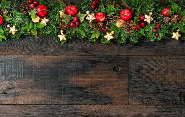 Świąteczne dekoracje złote gwiazdy zielone sosnowe gałęzie drewniane tła