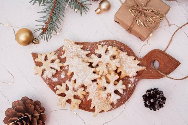 Świąteczne domowe ciasteczka do pieczenia w kształtach drzewa i płatki śniegu