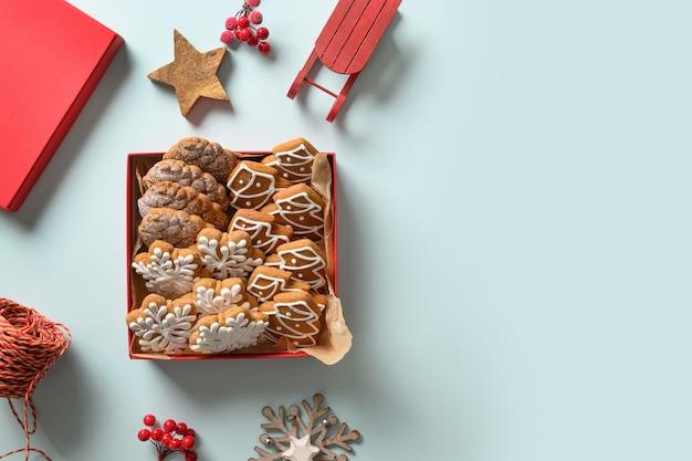 Świąteczne domowe ciasteczka szkliwione jako prezent w ozdobnym czerwonym pudełku na niebieskim tle. widok z góry. leżał na płasko. miejsce na tekst.