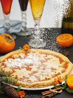 Świąteczne domowe ciasto z dżemem persimmon. ciasto ozdobione jest świątecznymi postaciami z ciasteczek. obok ciasta są plastry persimmon i choinka. zbliżenie.