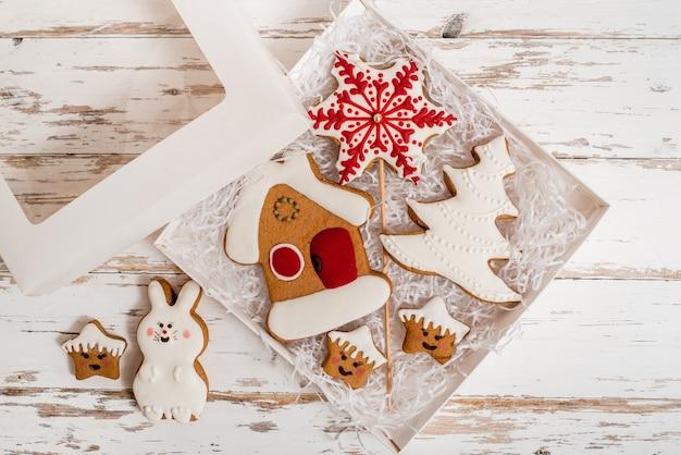 Świąteczne domowe pierniki na drewnianym stole. prezent noworoczny w pudełku, biała niespodzianka
