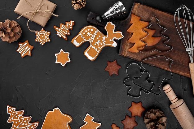Świąteczne domowe pierniki, przyprawy i deska do krojenia na ciemnym tle z miejsca kopiowania tekstu widok z góry. koncepcja wakacje, uroczystości i gotowania. pocztówka noworoczna i świąteczna