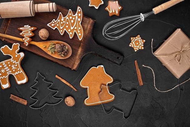 Świąteczne domowe pierniki przyprawy i deska do krojenia na ciemnym tle z miejscem na kopię...