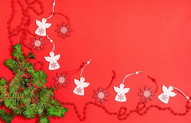 Świąteczne drewniane zabawki w postaci białego anioła i czerwonego płatka śniegu z jaskrawoczerwonymi koralikami, gałązka jodły na czerwonym tle. miejsce na miejsce na kopię, płaskie lay. widok z góry.