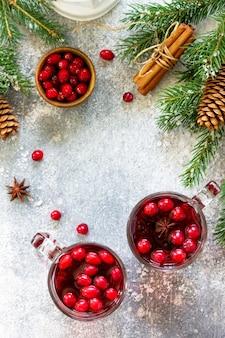 Świąteczne drinki gorący zimowy napój z żurawiną i cynamonem na jasnym kamiennym stole widok z góry
