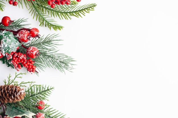 Świąteczne gałązki świerku layot, czerwone jagody i szyszki, posypane śniegiem, kopia przestrzeń