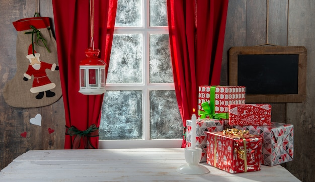 Świąteczne gify na stole, w pobliżu rustykalnego okna