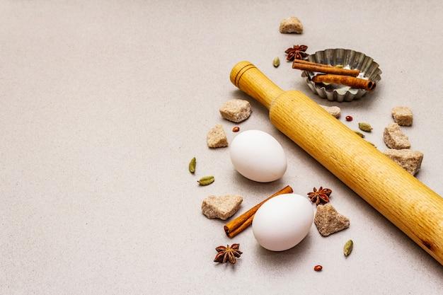 Świąteczne gotowanie, przyprawy, jajka, brązowy cukier w kawałkach, babeczka do pieczenia i wałek do ciasta. beton z lekkiego kamienia