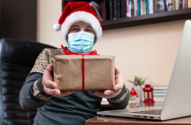 Świąteczne gratulacje online. młody człowiek w czapce świętego mikołaja i masce na twarz daje prezent i rozmawia za pomocą laptopa dla przyjaciół i dzieci połączeń wideo. boże narodzenie w okresie koronawirusa.