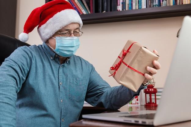Świąteczne gratulacje online. starszy mężczyzna w czapce świętego mikołaja i masce na twarz daje prezent i rozmawia za pomocą laptopa dla przyjaciół i dzieci połączeń wideo. boże narodzenie w okresie koronawirusa.