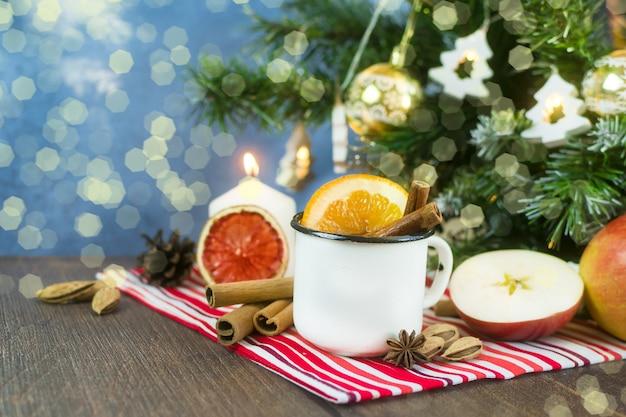 Świąteczne grzane wino bezalkoholowe gorący kompot w metalowym kubku z suszonymi owocami cynamonowymi pomarańczami