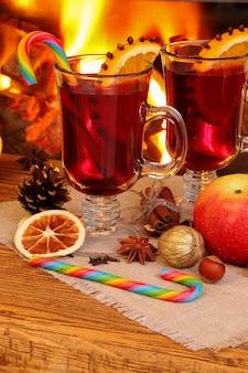 Świąteczne grzane wino - dwie szklanki na tle płonącego kominka