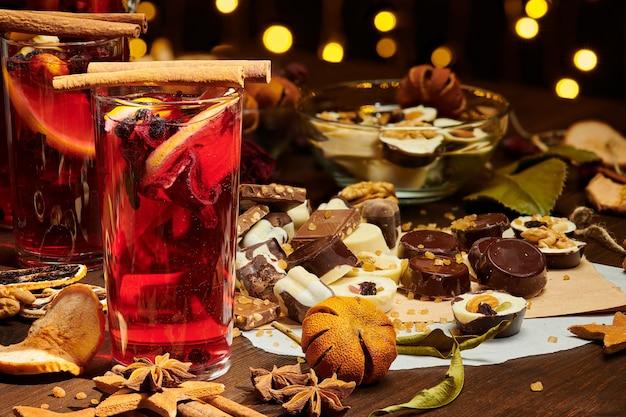 Świąteczne grzane wino lub gluhwein z przyprawami, czekoladowymi słodyczami i plasterkami pomarańczy