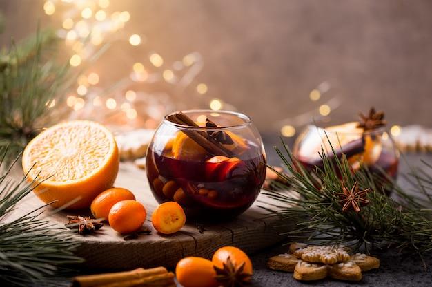 Świąteczne grzane wino w okrągłych kieliszkach pyszne wakacje jak imprezy z pomarańczowymi przyprawami anyżu cynamonowego. tradycyjny gorący napój w szklankach lub napoju w kształcie koła, świąteczny koktajl na x-masie lub w nowym roku