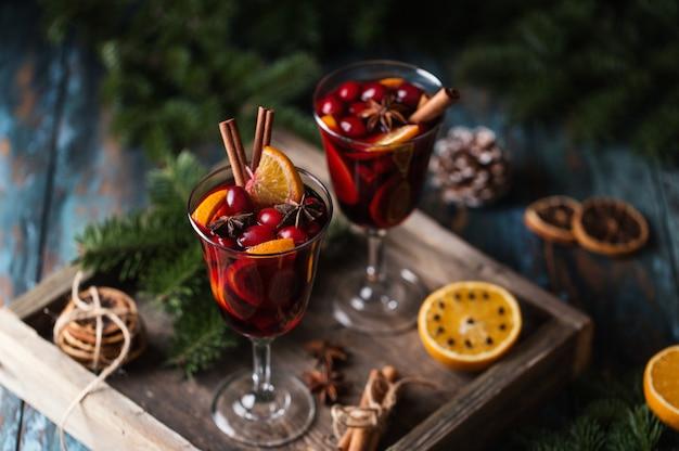 Świąteczne grzane wino w szklance z przyprawami, owocami cytrusowymi i żurawiną. świąteczna atmosfera.