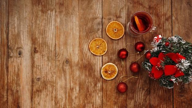 Świąteczne grzane wino w szklanym kubku na drewnianym stole z suszonymi pomarańczami