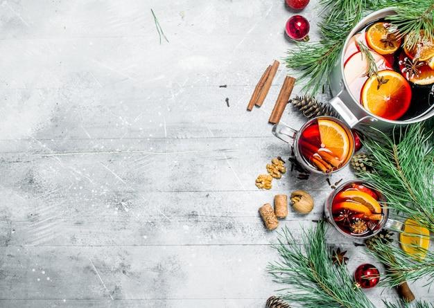 Świąteczne grzane wino z aromatycznymi przyprawami. na rustykalnym stole.