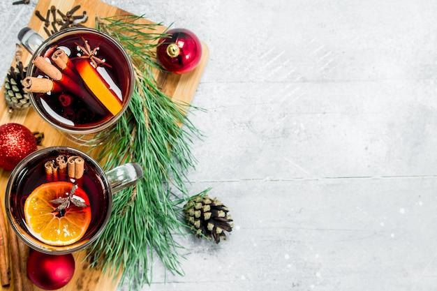 Świąteczne grzane wino z aromatycznymi przyprawami. na rustykalnym tle.