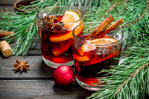 Świąteczne grzane wino z dodatkiem przypraw i aromatycznych ziół. na drewnianym.