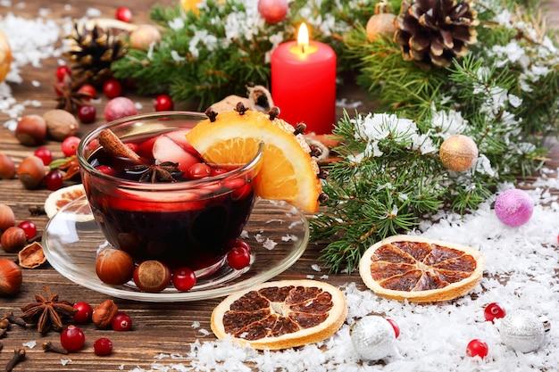 Świąteczne grzane wino z jabłkiem, żurawiną, pomarańczą i przyprawami na drewnianym stole
