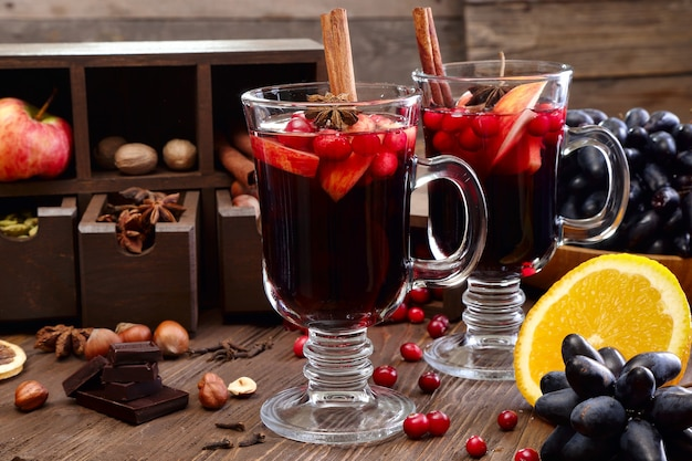 Świąteczne grzane wino z jabłkiem, żurawiną, pomarańczą, przyprawami i czekoladą na drewnianym stole