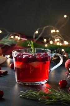 Świąteczne grzane wino żurawinowe i jabłkowe ozdabiają rozmaryn i gałęzie jodły