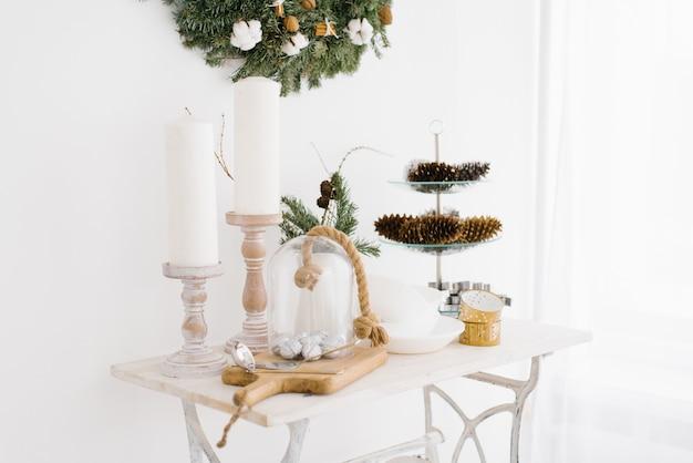 Świąteczne i noworoczne dekoracje na stoliku do kawy w salonie w domu. świece i stożki