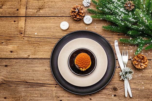 Świąteczne i noworoczne nakrycie obiadowe. słodka przekąska, gałąź jodły, świece, szyszki, płytki ceramiczne, widelec i nóż.