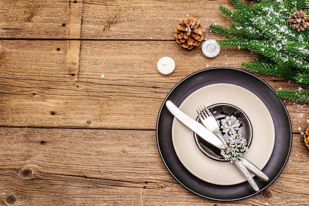 Świąteczne i noworoczne nakrycie obiadowe. zimozielona gałąź jodły, świece, stożki, płytki ceramiczne, widelec i nóż.