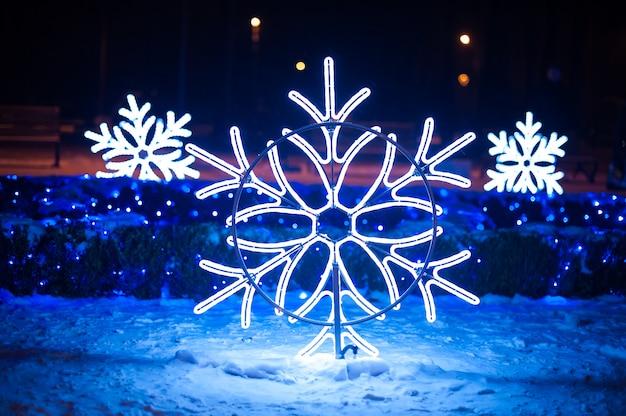 Świąteczne iluminacje w postaci płatków śniegu w nocnym parku