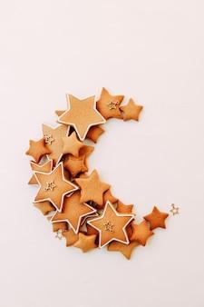 Świąteczne imbirowe ciasteczka w kształcie gwiazdek posypane ciasteczkami w kształcie księżyca na białym