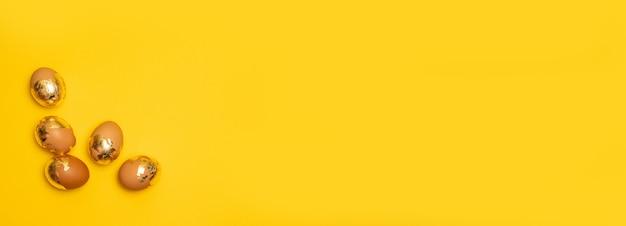 Świąteczne jajka wielkanocne złote i brązowe. koncepcja wesołych świąt. widok z góry na płasko.