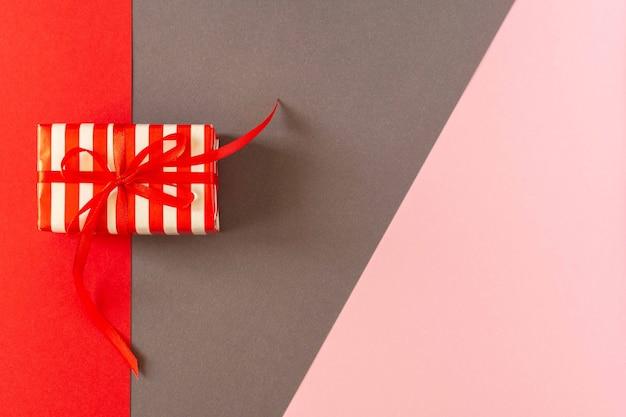 Świąteczne jasne kolorowe tło, prezent ze wstążką i kokardą na kolorowych papierach