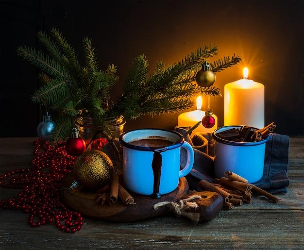 Świąteczne jedzenie i dekoracje. futrzane gałęzie, kubek gorącej czekolady, kolorowe szklane kulki, płonące świece, laski cynamonu, ciemne