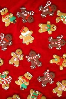 Świąteczne jedzenie piernikowe ludziki ciasteczka bożonarodzeniowe czerwone tło widok z góry retro moder...