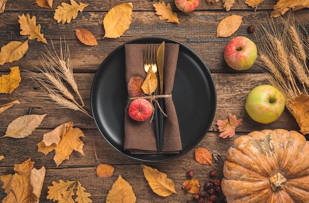 Świąteczne jesienne tło z talerzem serwującym serwetkowe sztućce z dynią i jesiennymi liśćmi