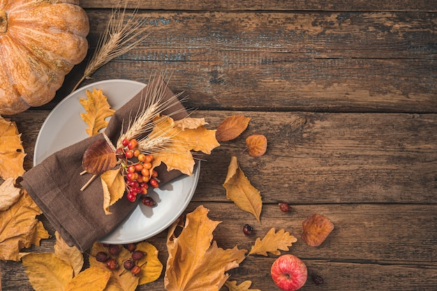 Świąteczne jesienne tło z talerzem sztućce serwetka dynia i jesienne liście na drewnianym tle