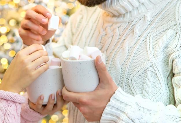 Świąteczne kakao z piankami w rękach mężczyzny i kobiety. selektywne skupienie. wakacje.