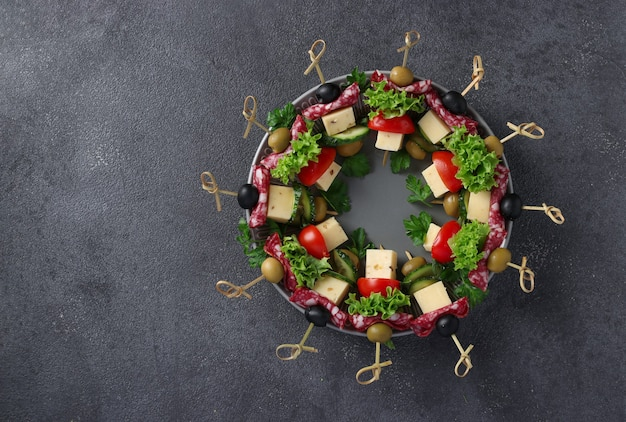 Świąteczne kanapki z kiełbasą, ogórkami, pomidorami, oliwkami i serem, podawane na talerzu jako wieniec bożonarodzeniowy, na ciemnym tle. widok z góry