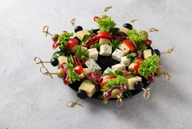 Świąteczne kanapki z kiełbasą, ogórkami, pomidorami, oliwkami i serem, podawane na talerzu jako wieniec bożonarodzeniowy, na jasnoszarym tle.