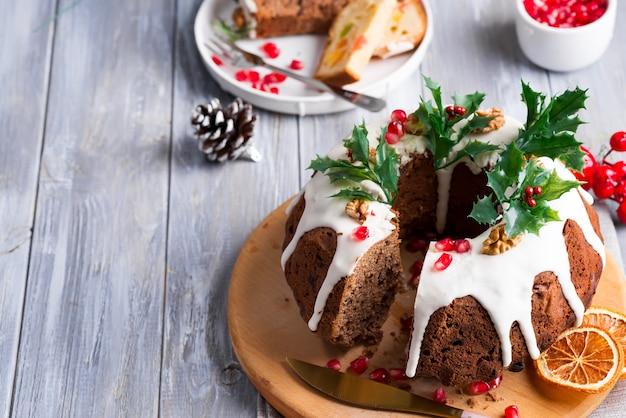 Świąteczne krojone ciasto czekoladowe z białym lukrem, gałązkami ostrokrzewu i ziarnami granatu szary drewniany